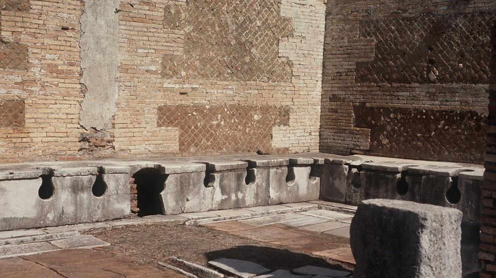 Öffentliche römische Bedürfnisanstalt mit integrierter Wasserspülung.