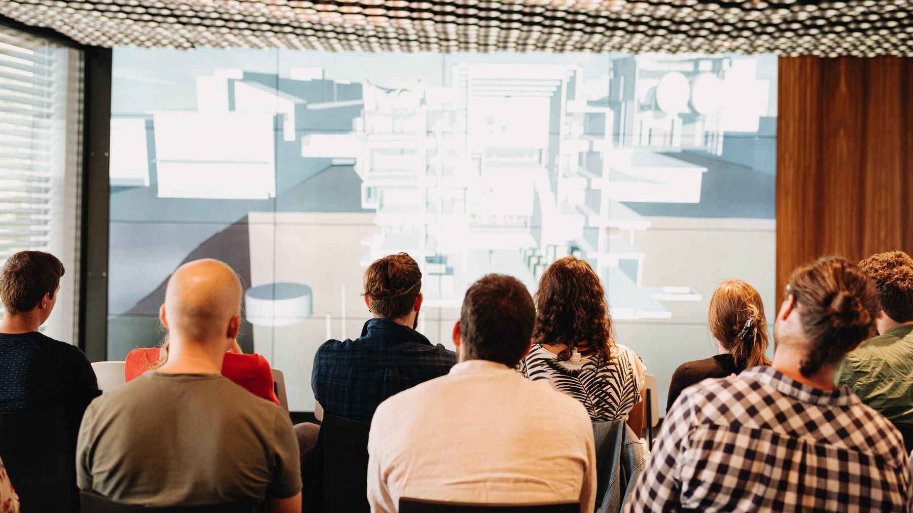 Personen verfolgen eine Präsentation an einer Fachtagung